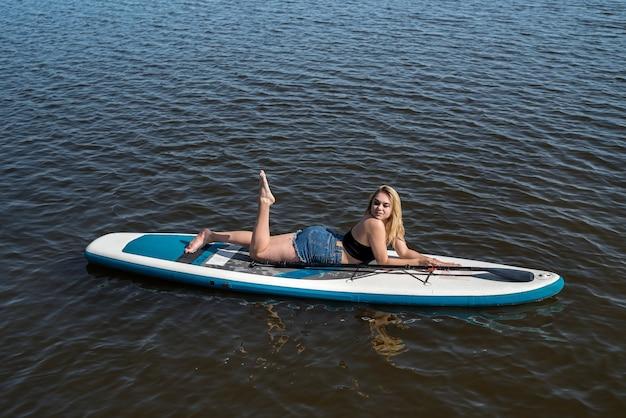暑い夏の日にsupボードに横たわっているかなり若い女性。自由