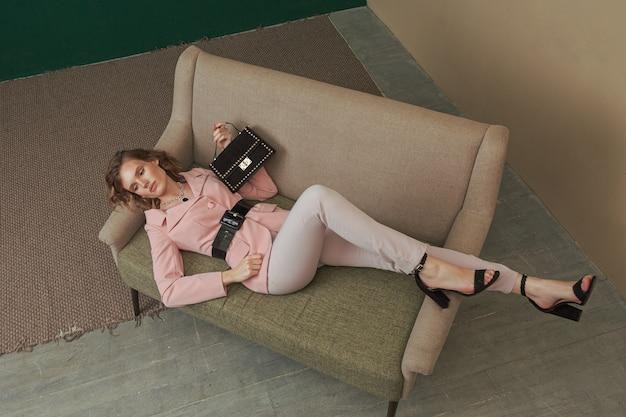 小さな暗いベルベットのハンドバッグを備えたスタイリッシュなスマートカジュアルな服装でソファに横になっているかなり若い女性。