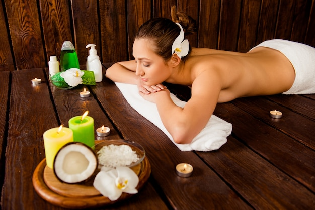 Pretty young woman lying in sauna and relaxing