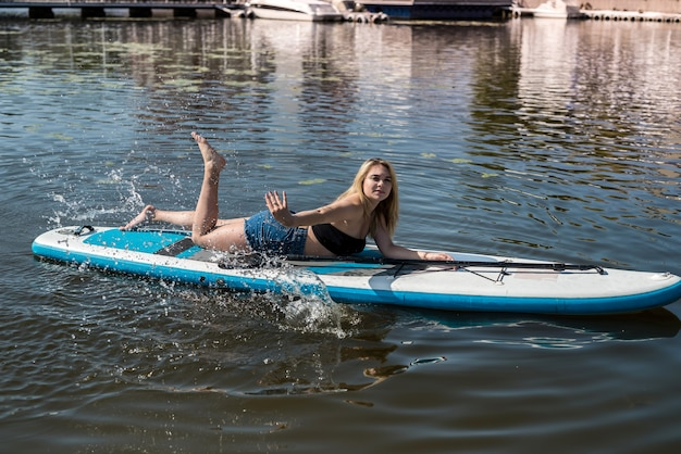 Pretty young woman lying on a sup board on hot summer day. freedom