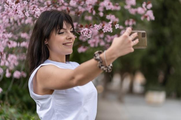 かなり若い女性がスマートフォンで自分撮りをします