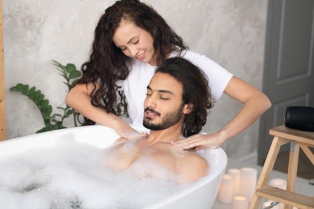 Довольно молодая женщина делает массаж шеи и плеч своему мужу, расслабляющемуся в ванне с горячей водой и пеной