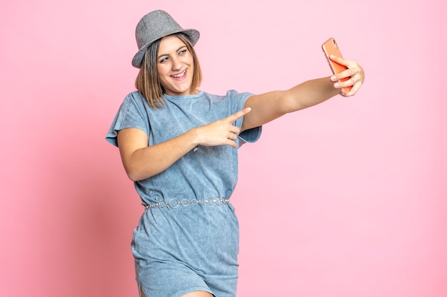 Pretty young woman making a self portrait with smartphone on pink