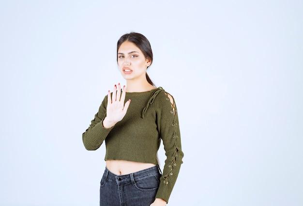 Donna abbastanza giovane che media con espressione seria sulla parete bianca