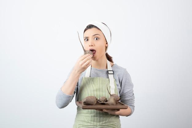 Modello di donna abbastanza giovane in grembiule che mangia una barbabietola.