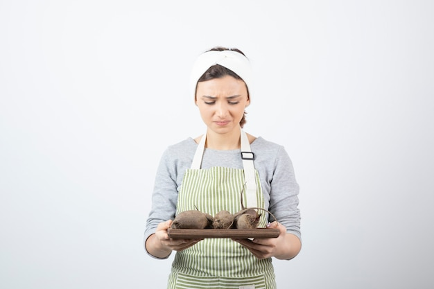 Modello di donna abbastanza giovane in grembiule che tiene una tavola di legno con barbabietole.