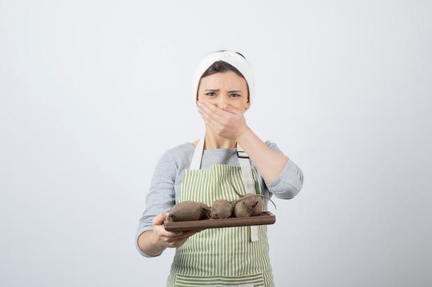 Modello di donna abbastanza giovane in grembiule con una tavola di legno di barbabietole che copre la bocca.