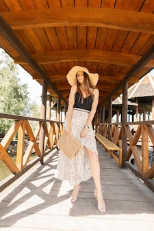 빈티지 레이스 란제리의 세련된 짠 핸드백과 아름다운 섹시한 다리가 있는 빈티지 드레스가 있는 밀짚모자를 쓴 예쁜 젊은 여성 모델은 해변 근처의 나무 부두에 서 있습니다