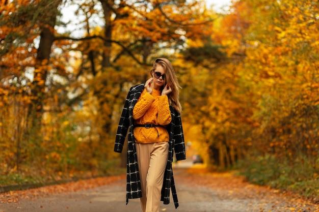 노란색 니트 스웨터를 입은 세련된 코트에 헤어스타일을 한 예쁜 젊은 여성 모델은 선글라스를 쓰고 가을 단풍으로 공원을 산책합니다.