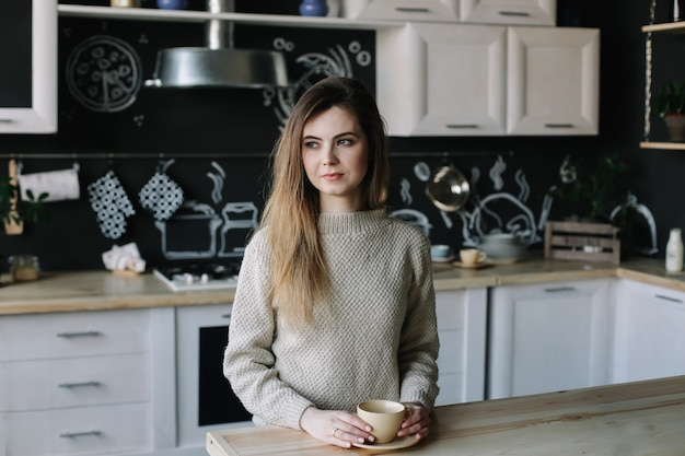 Pretty young woman in the modern kitchen interior