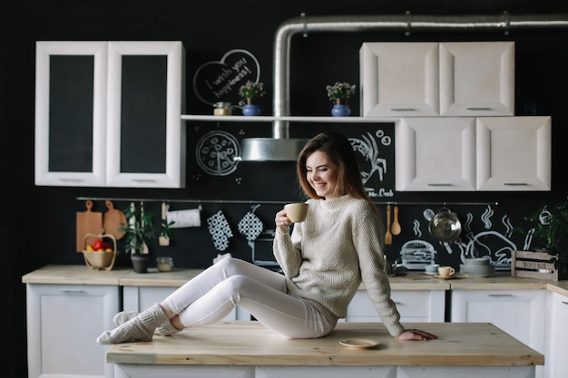 A pretty young woman in the modern kitchen interior