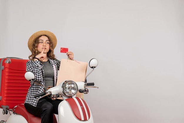 Pretty young woman on moped holding card on grey
