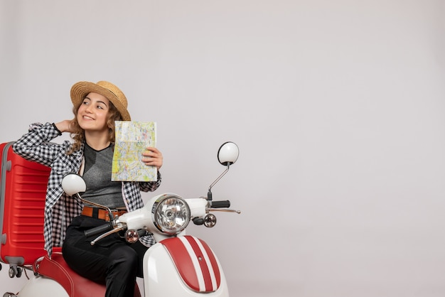 Pretty young woman on moped holding map on grey