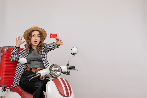 Pretty young woman on moped holding up card on grey isolated