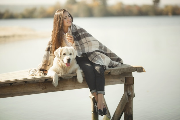 Pretty young woman outdoors with dog. golden retriever and his owner resting near the water and drinking tea