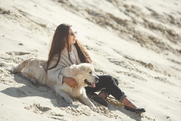 Pretty young woman outdoors with dog. golden retriever and his owner resting