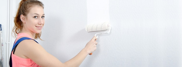 Pretty young woman painting the wall white color