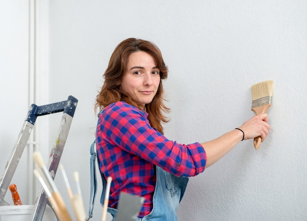 Pretty young woman painting wall white color
