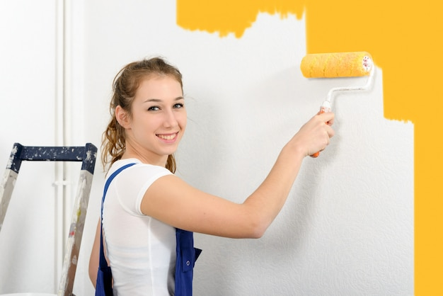 Pretty young woman paints the wall on orange