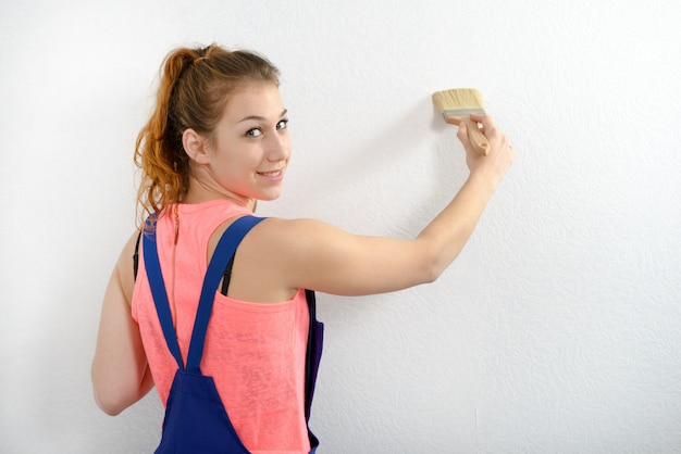 Pretty young woman paints the wall white color