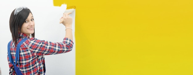 Pretty young woman paints the wall yellow color, horizontal photo banner