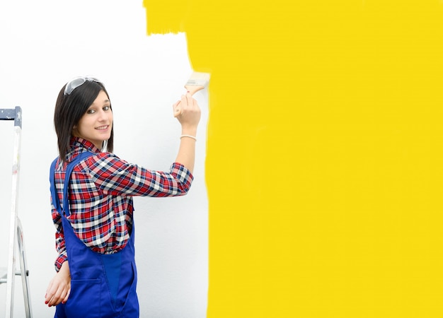 Pretty young woman paints the wall yellow color