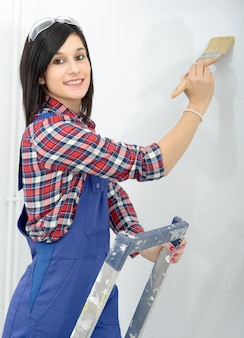 Pretty young woman paints the wall