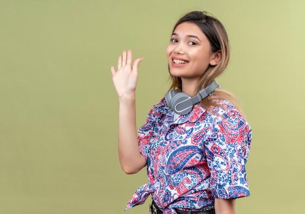 Una bella giovane donna in camicia stampata paisley che indossa le cuffie sorridendo e mostrando il gesto di addio su una parete verde