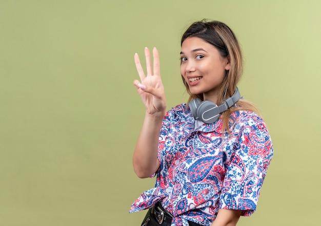 Una bella giovane donna in camicia stampata paisley che indossa le cuffie sorridendo e mostrando tre numeri su una parete verde