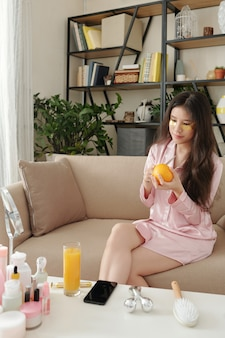 Pretty young woman in pajamas sitting on sofa with undereye patches and cutting orange for breakfast