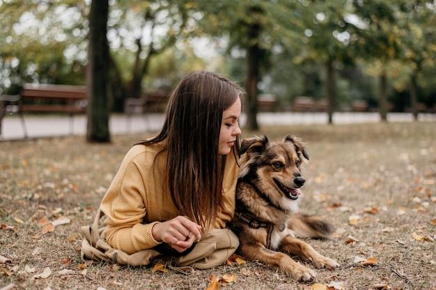 Довольно молодая женщина гладит свою собаку