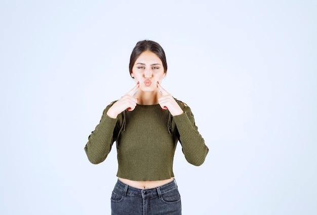 Довольно молодая женщина, пощипывая щеки на белой стене Бесплатные Фотографии
