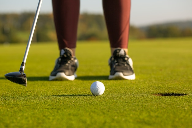 Pretty young woman playing golf on training ground, hits the golf ball into the hole, sport concept