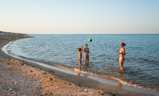 Pretty young woman plays ball with her charming daughters while swimming in the sea on a sunny warm summer day