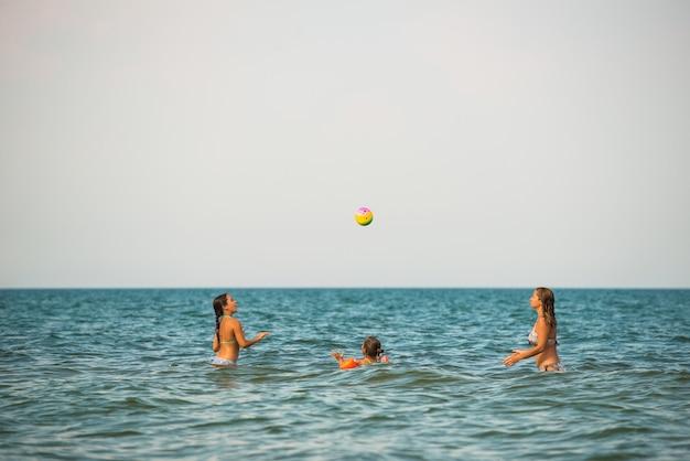 Довольно молодая женщина играет в мяч со своими дочерьми