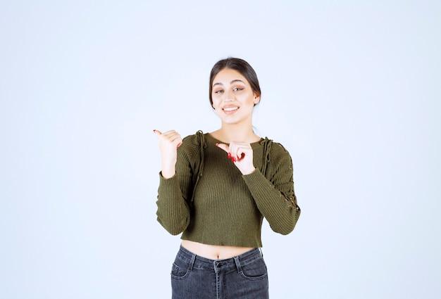 白い壁に彼女の側を指しているかなり若い女性