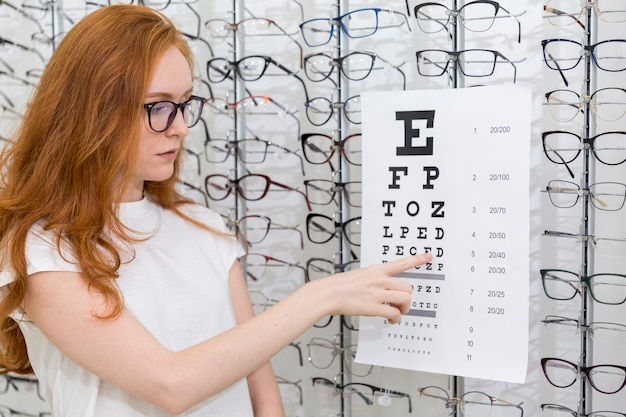 Довольно молодая женщина, указывая письмо на графике снеллен в магазине оптики