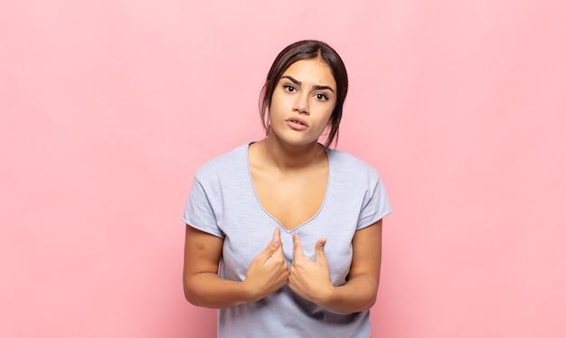 Симпатичная молодая женщина, озадаченная и озадаченная, указывая на себя, потрясенная и удивленная, что ее выбрали