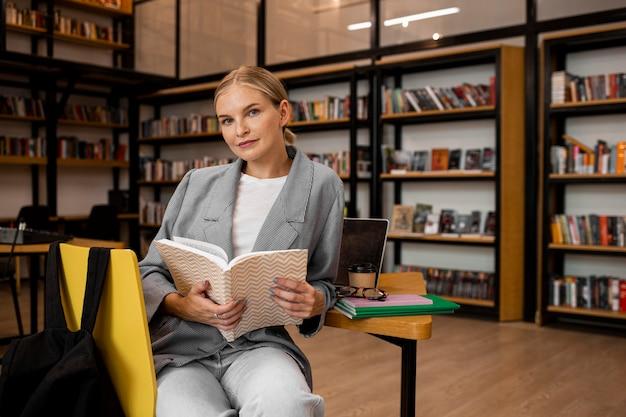 Довольно молодая женщина позирует в библиотеке