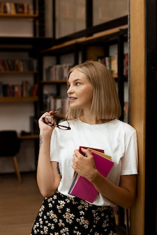 Bella giovane donna in posa in biblioteca