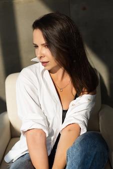 Довольно молодая женщина позирует на белом стуле в студии