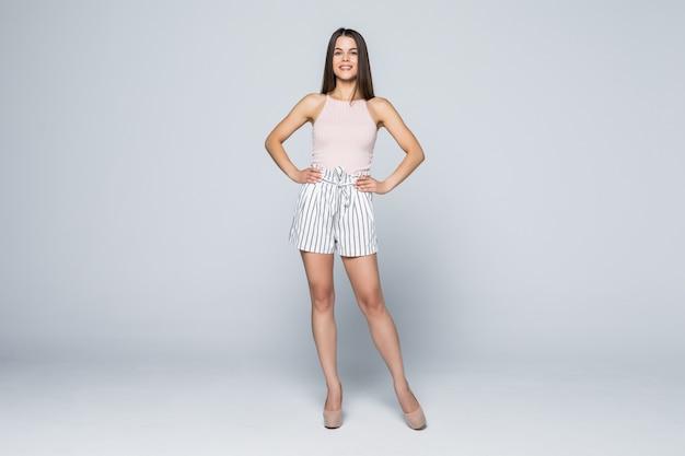 Bella giovane donna in posa in pantaloncini di jeans sexy, isolato su bianco in tutta la lunghezza