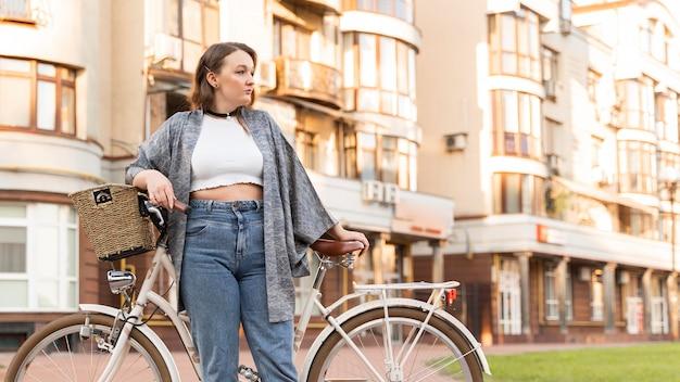 Довольно молодая женщина позирует с велосипедом