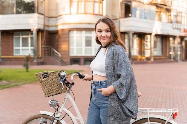 Donna abbastanza giovane che posa con la bici