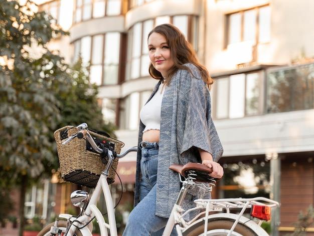 자전거와 함께 포즈를 취하는 예쁜 젊은 여자