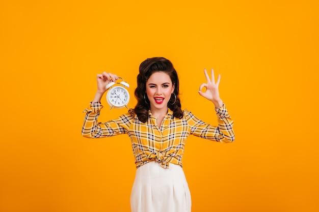 時計と大丈夫サインでポーズをとるかなり若い女性。黄色の背景の上に立っている市松模様のシャツの笑顔のピンナップガール。
