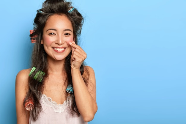 Pretty young woman posing with hair curlers
