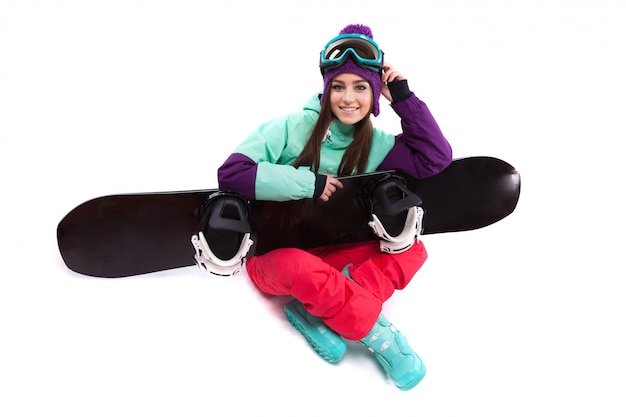 Pretty young woman in purple ski costume siting cross-legged with snowboard