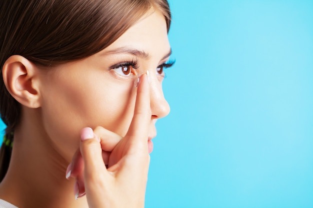 Pretty young woman puts on contact lenses for eyesight