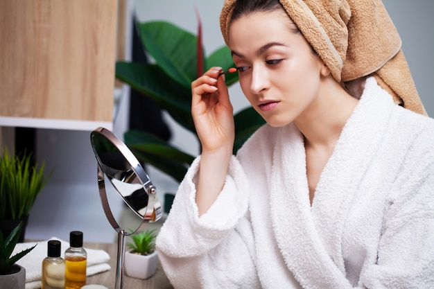Pretty young woman puts makeup on the face in the bathroom